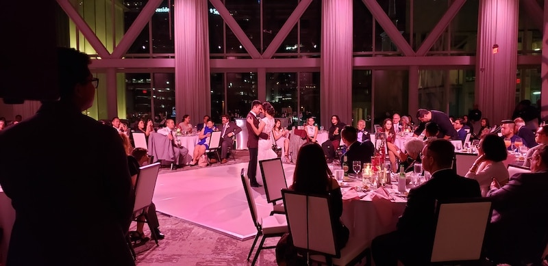 bride and groom sharing their first dance while guests watch from their tables