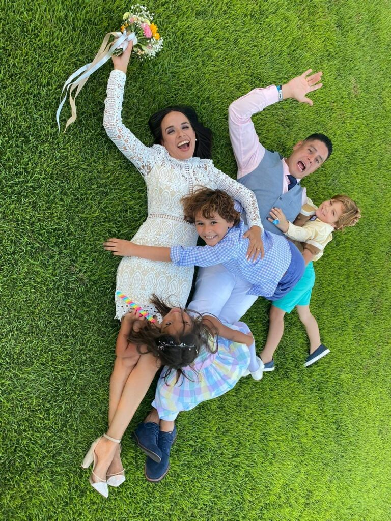 bride groom with kids laying on grass