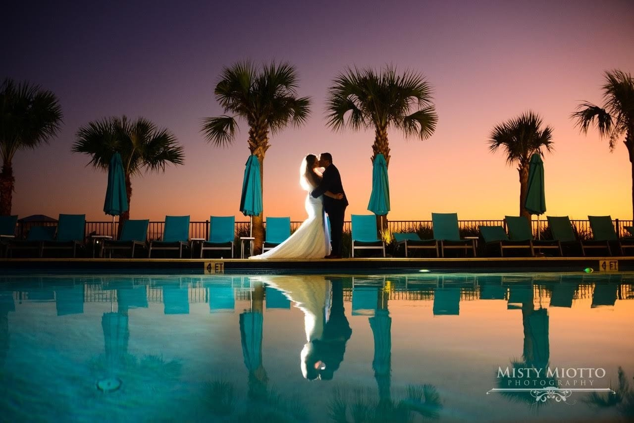 couple kissing by pool at sunset