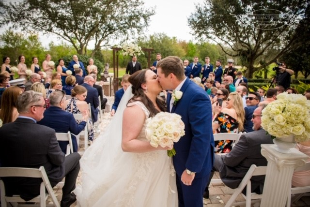 bride & room kissing at ceremony