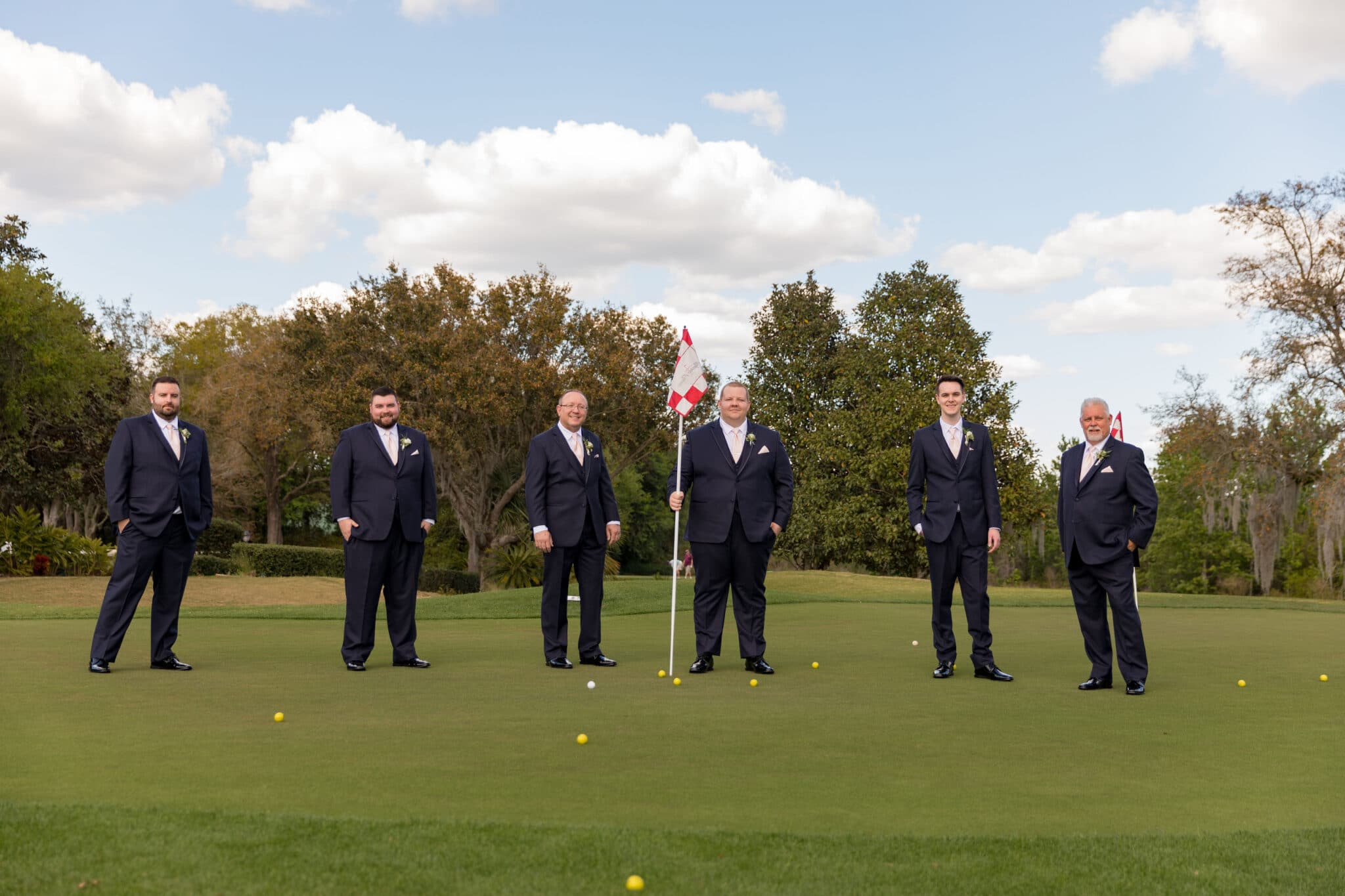 groomsmen standing on golf course with flag