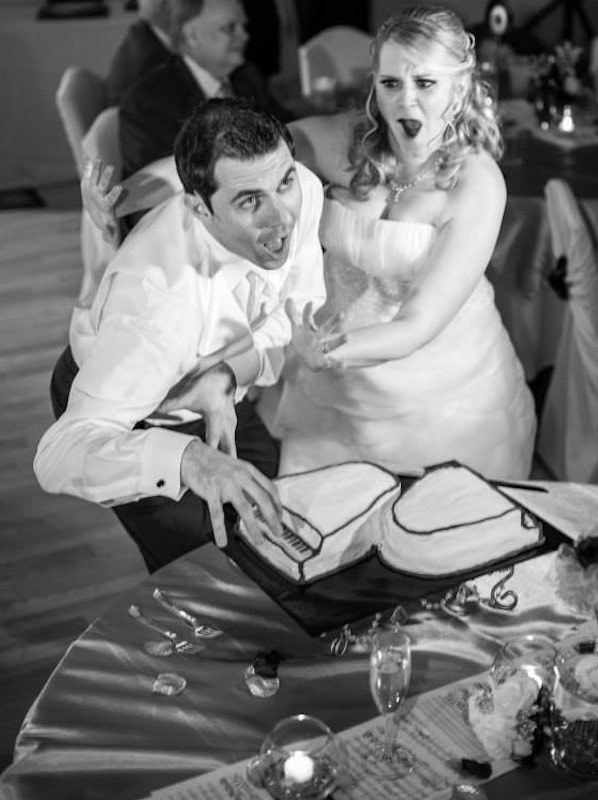 groom pretending to play a cake made to look like a piano while his bride acts shocked