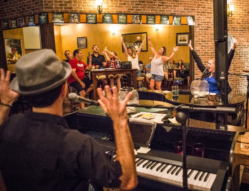 Randy waving to patrons at Irish bar while performing on the piano