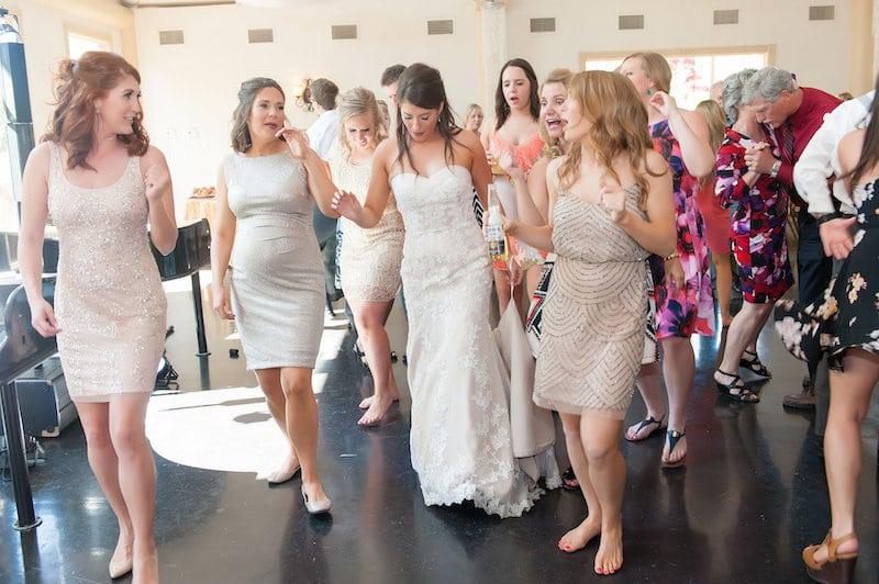bride and her guests dancing to music from dueling pianos