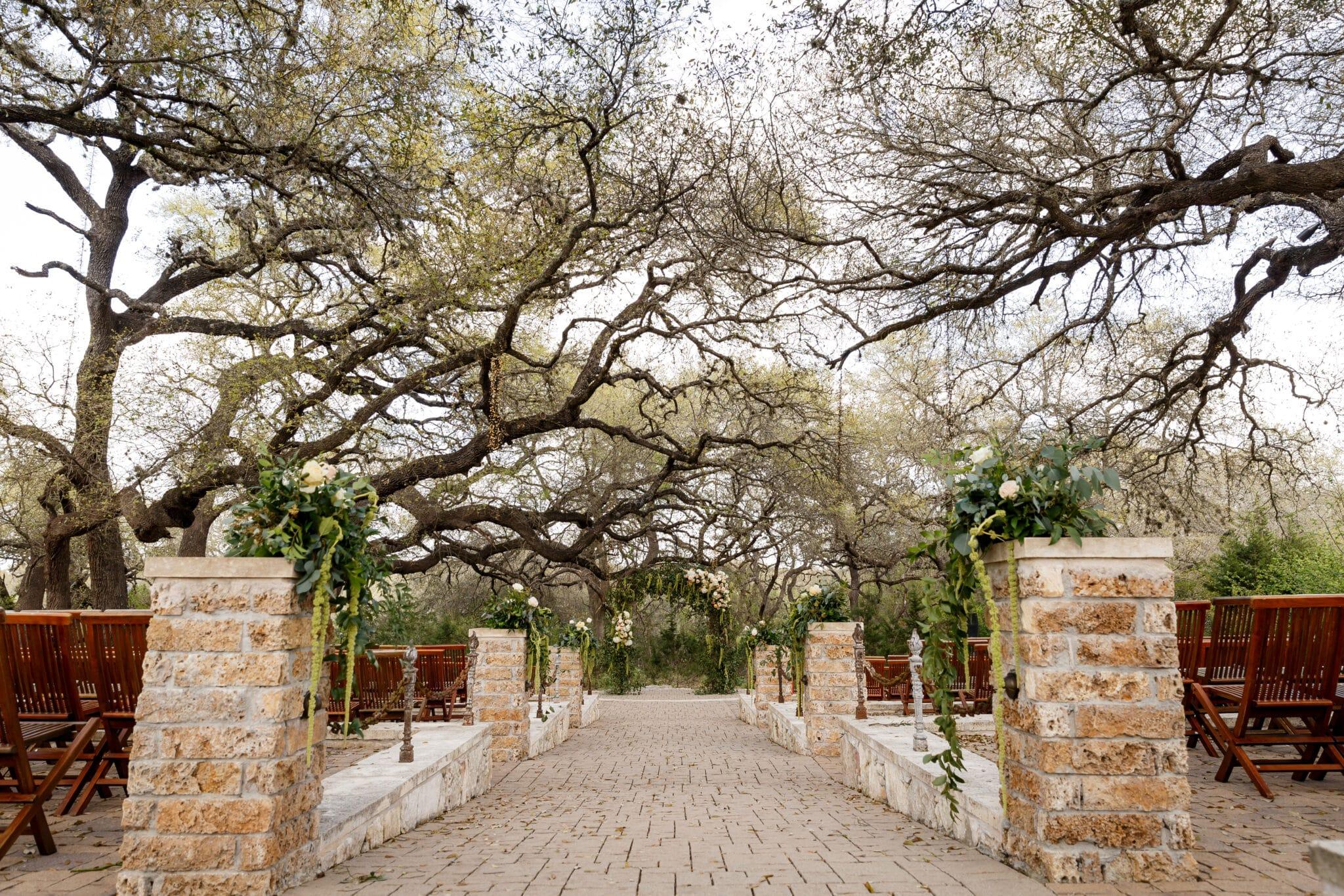 destination wedding ceremony venue with oak tree canopy and stone aisle