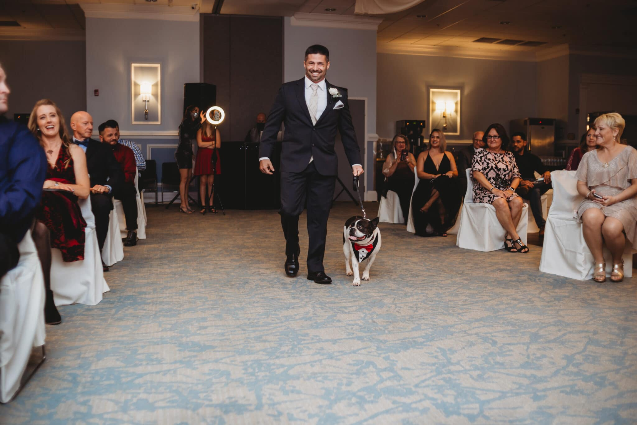 groom walking dog down the aisle of ceremony