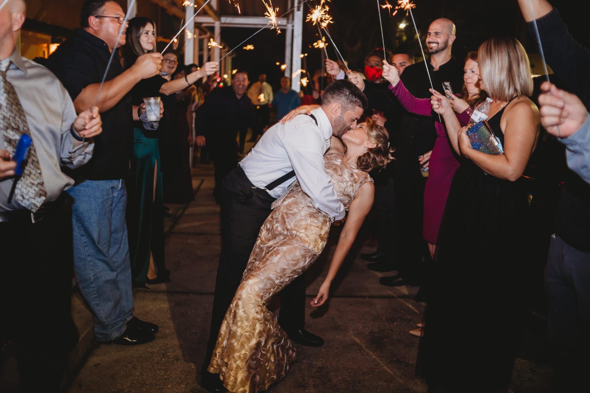 bride and groom kissing under sparklers