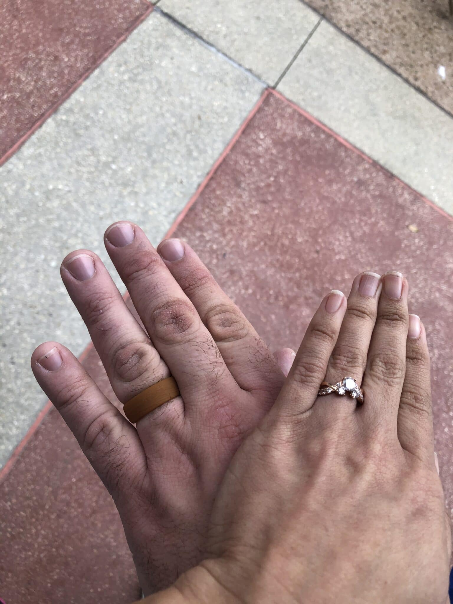 womans hand on top of mans hand both with new rings on fingers after marriage proposal