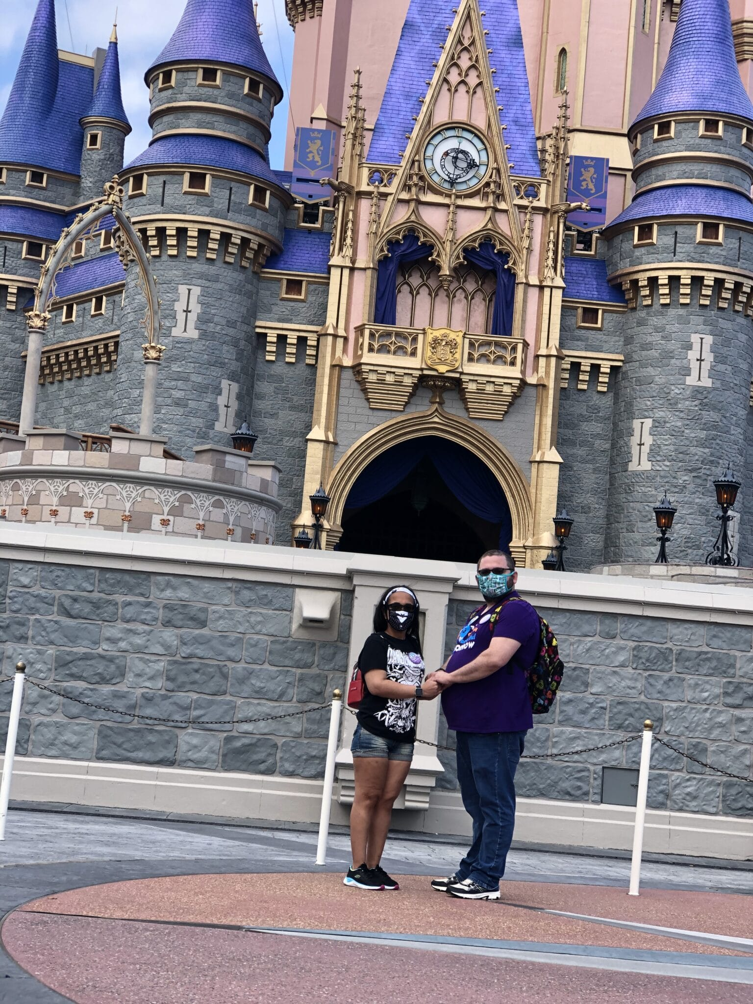 man and woman stand together holding hands in front of cinderellas castle at walt disney worlds magic kingdom