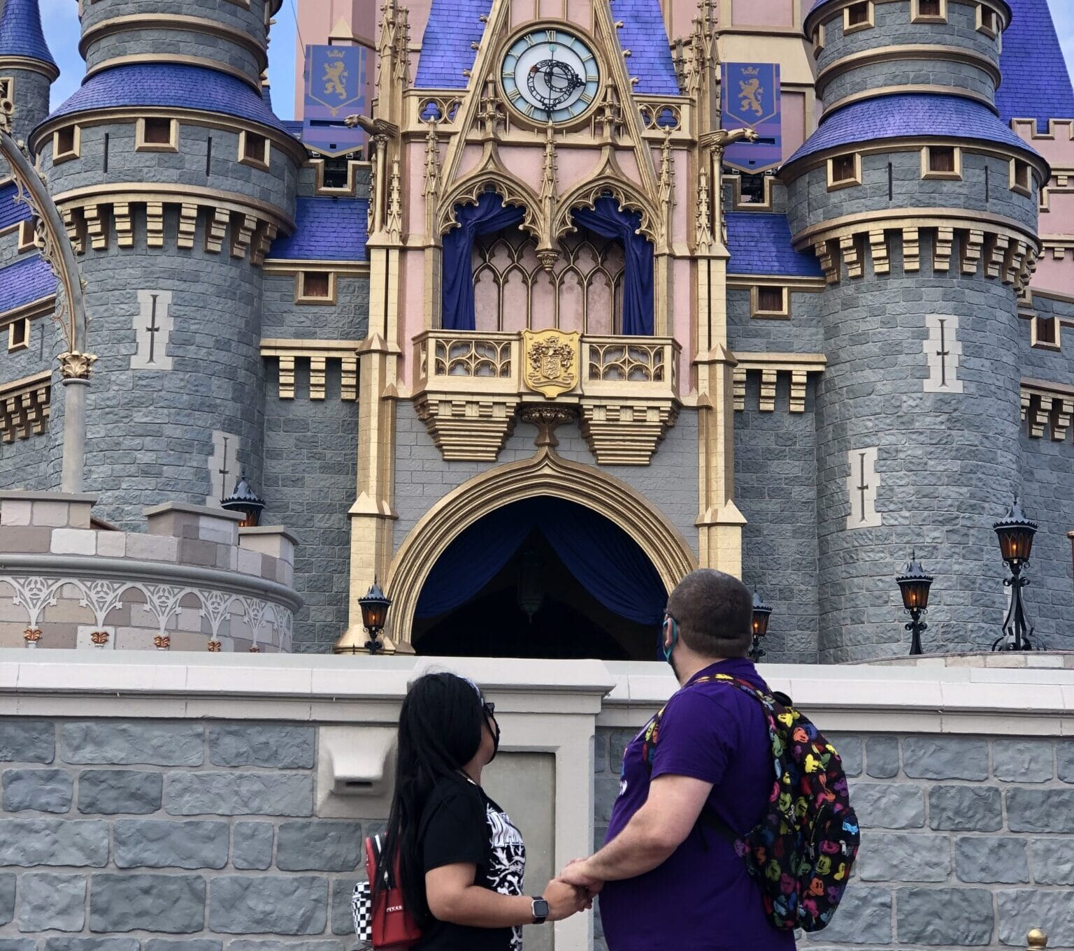 couple stand with their bodies facing each other looking up at cinderella's castle after magical disney marriage proposal