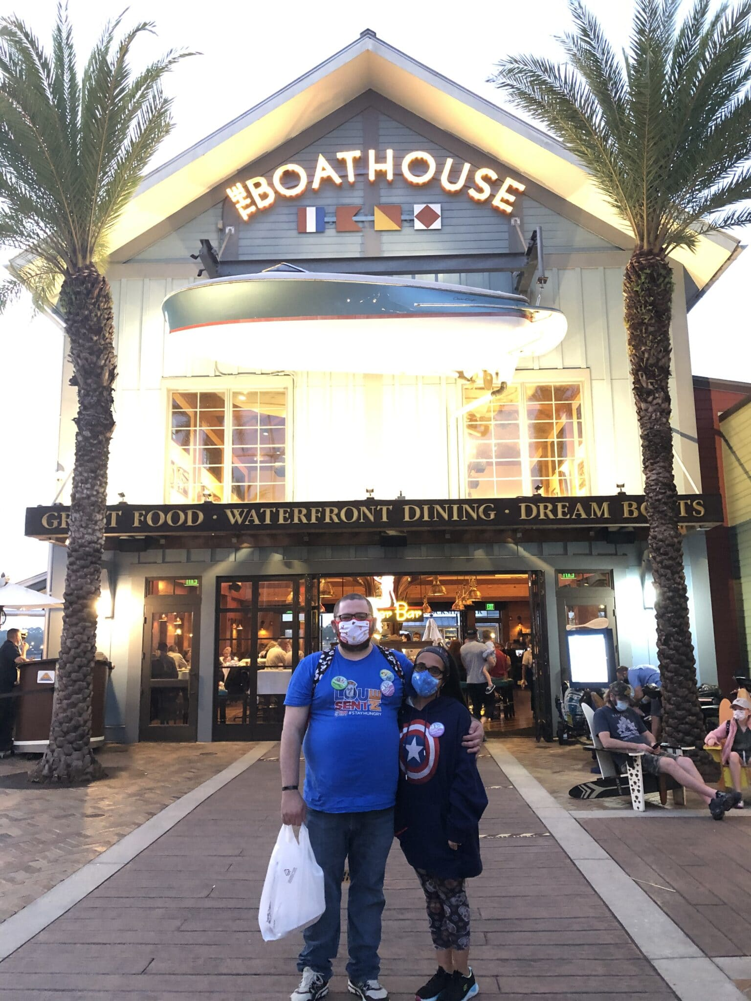 couple stands together wearing marvel shirts in front of boathouse restaurant in disney springs orlando