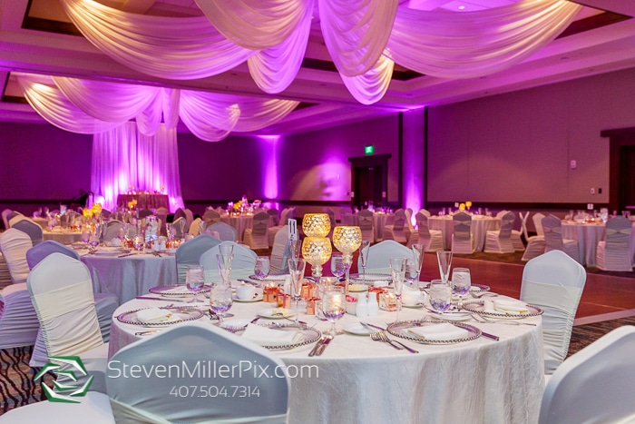 ballroom with drapery, pink lighting, and white tables with candles set up for wedding reception