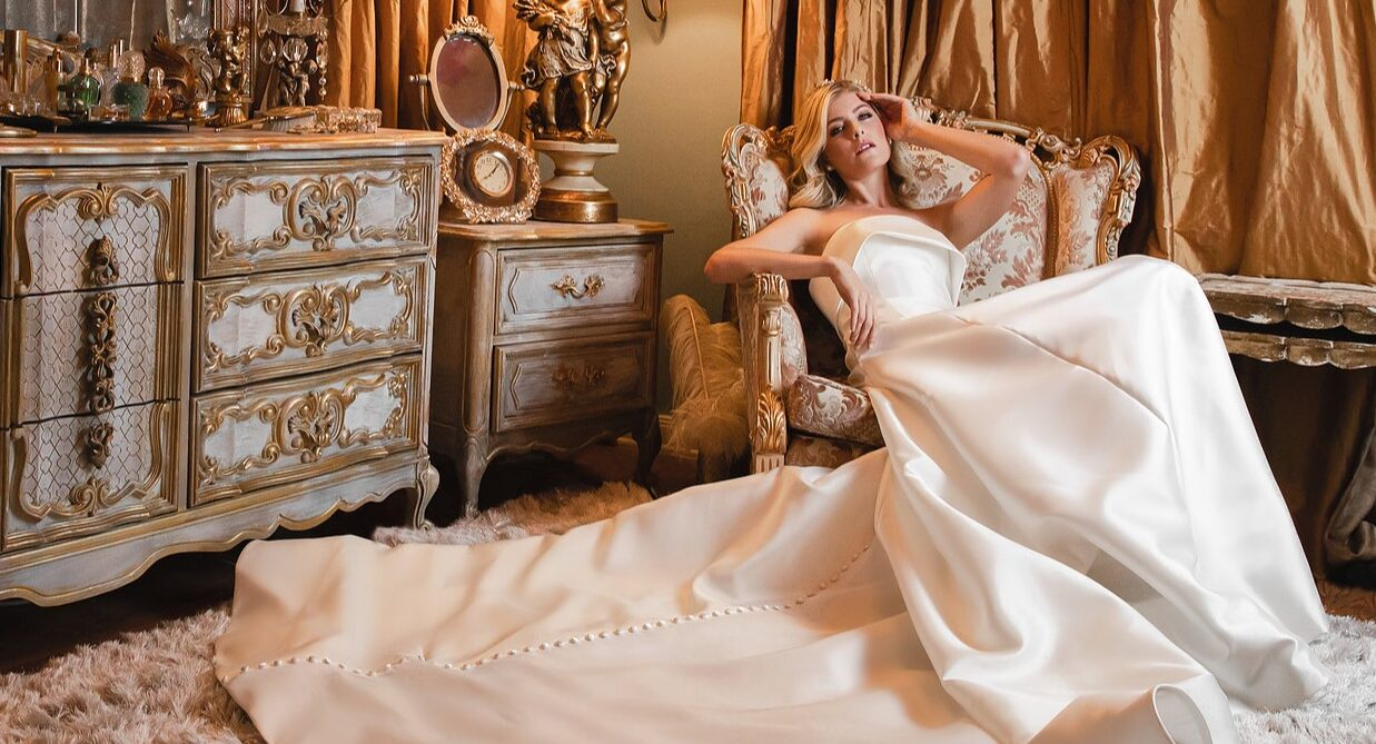 bride sitting in an upholstered chair in a room with gold curtains