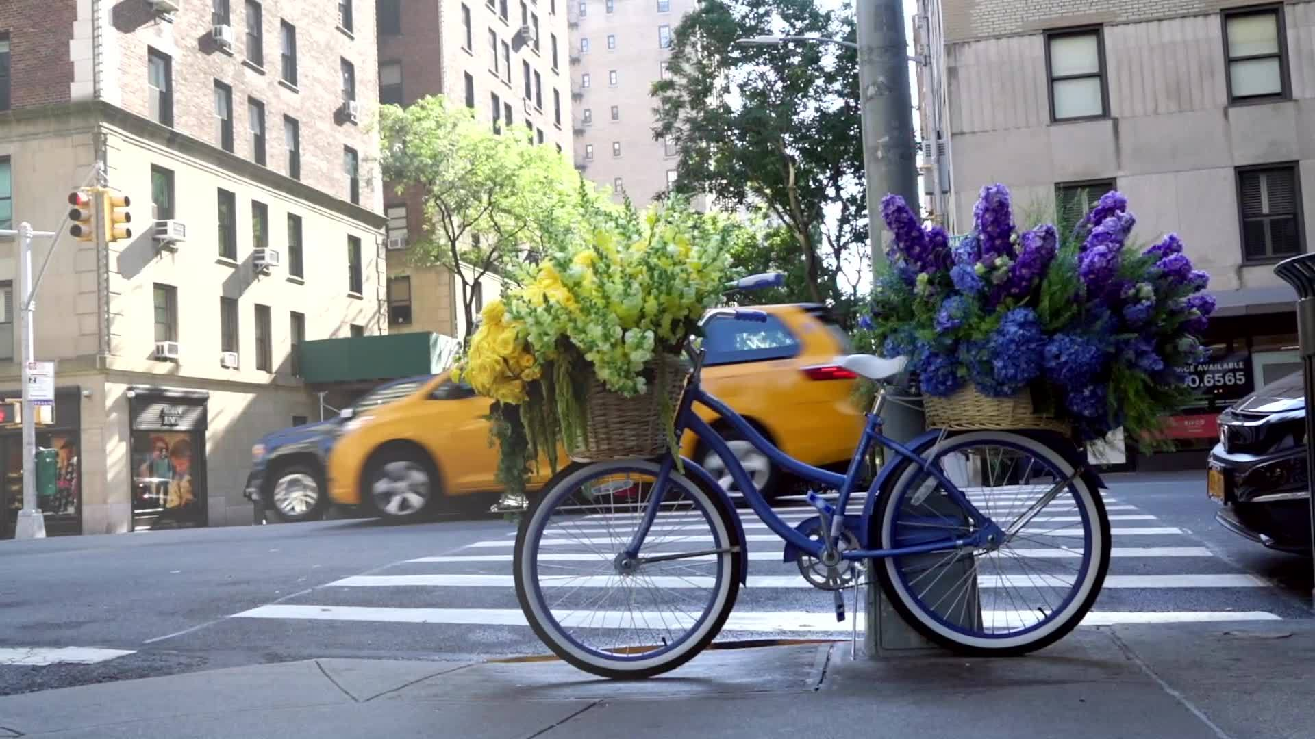 blue bicycle with flowers on both the front and back wheels