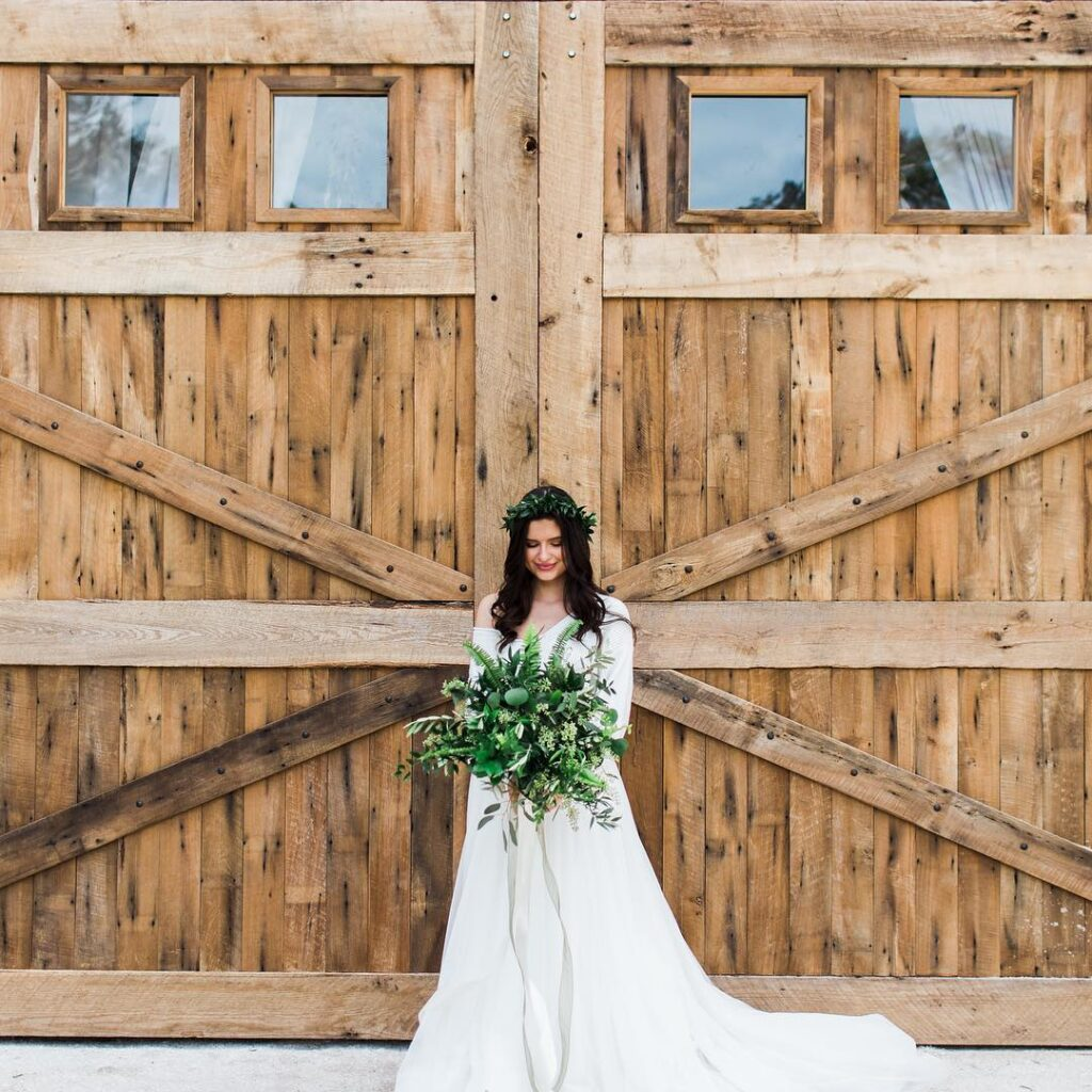 bride with floral crown holding large greenery bouquet in front of rustic wooden barn doors