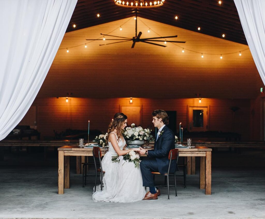 bride and groom sitting in chairs facing each other and holding hands inside barn wedding