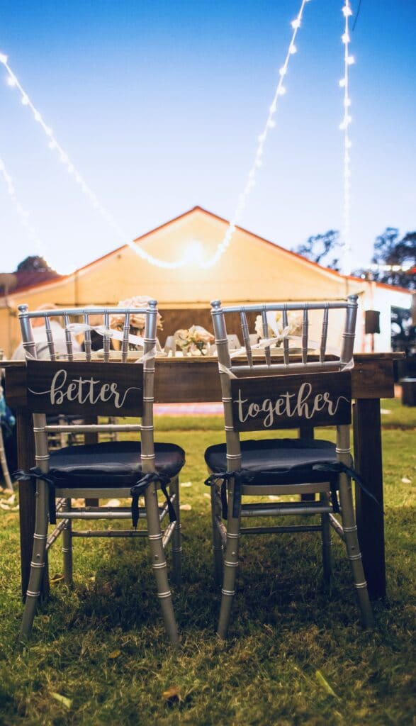 sweetheart table set up for outside wedding with signs on the back of the bride and groom's chairs that read better together