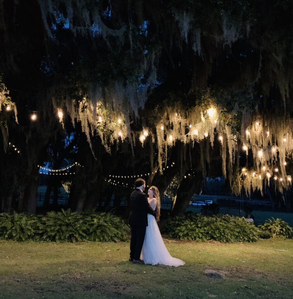 bride and groom dancing underneath some large trees lit with market lighting