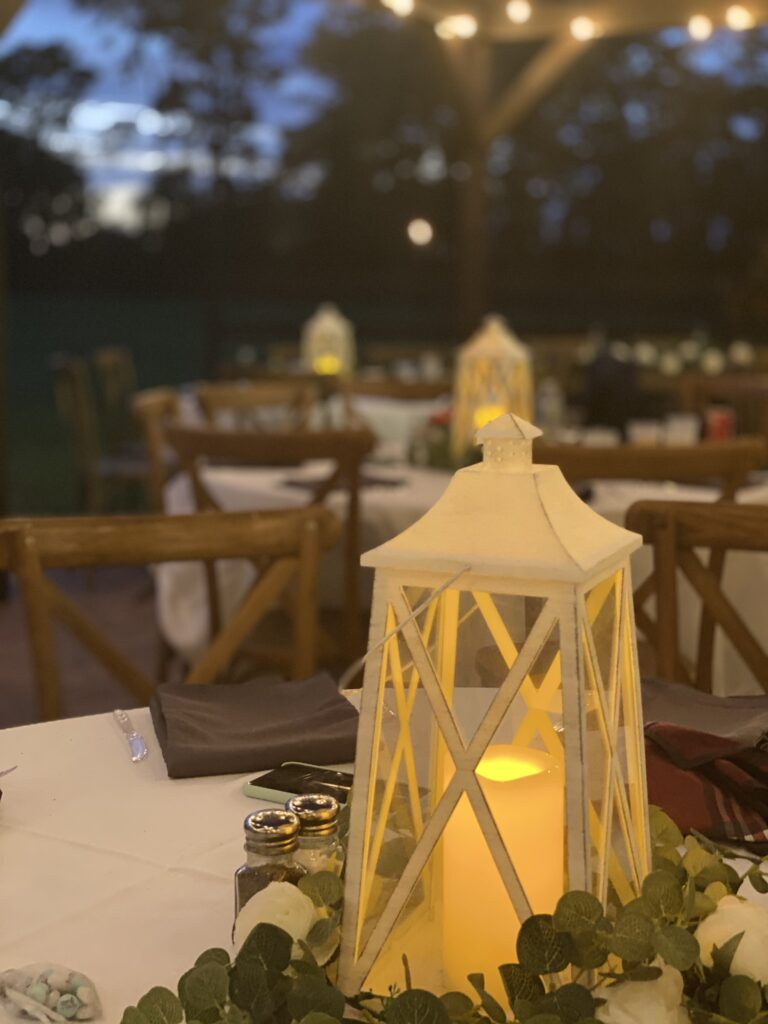tables set up for a wedding reception, let with a candle and lantern on each table and market lights above the tables