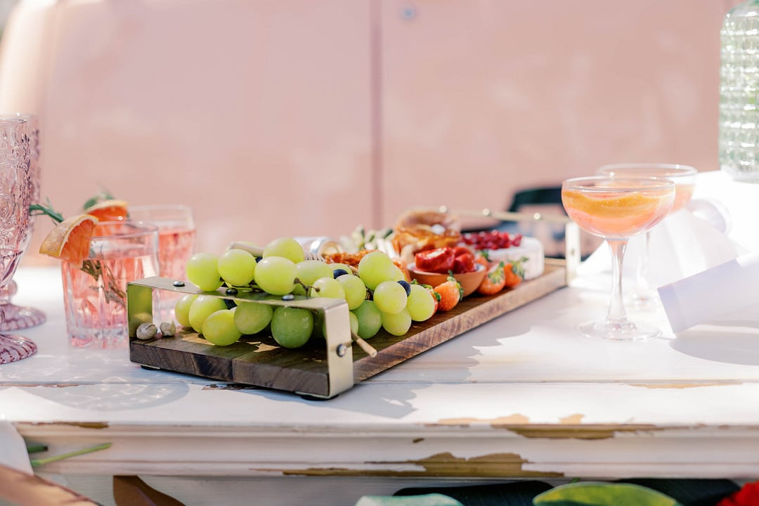 fruit meat and cheese arranged on wooden plank board sitting out with drinks in glasses on a table top