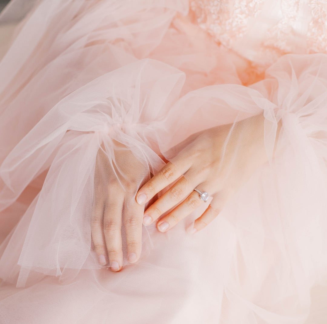 light skin colored hands together with ring on engagement fingers on top of fluffly light pink material