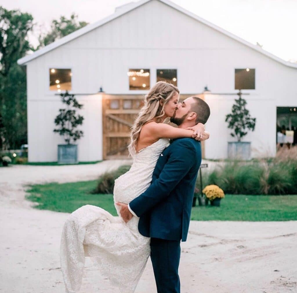 groom picking up bride and kissing her in front of white barn