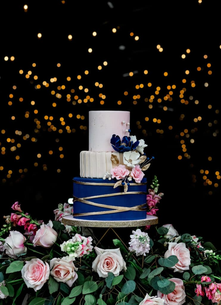beautiful wedding cake with flowers around the base of the cake stand