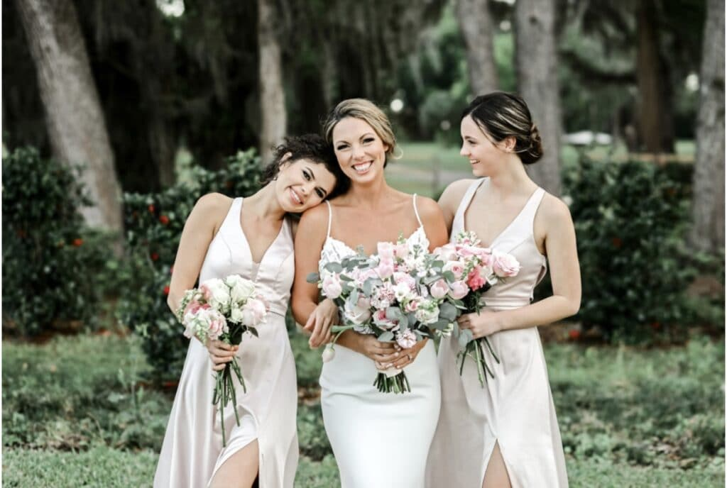 bride standing with her bridesmaids next to her