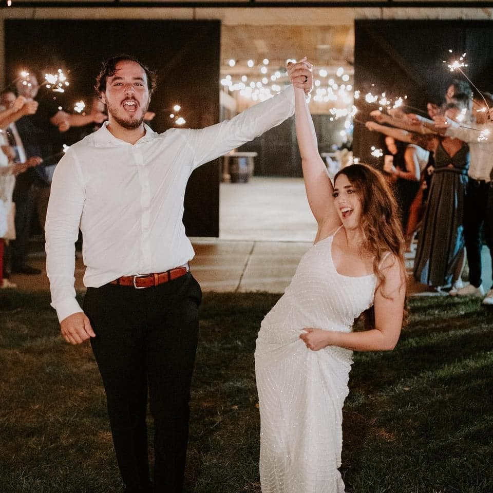 bride and groom celebrating while their guests hold lit sparklers and cheer