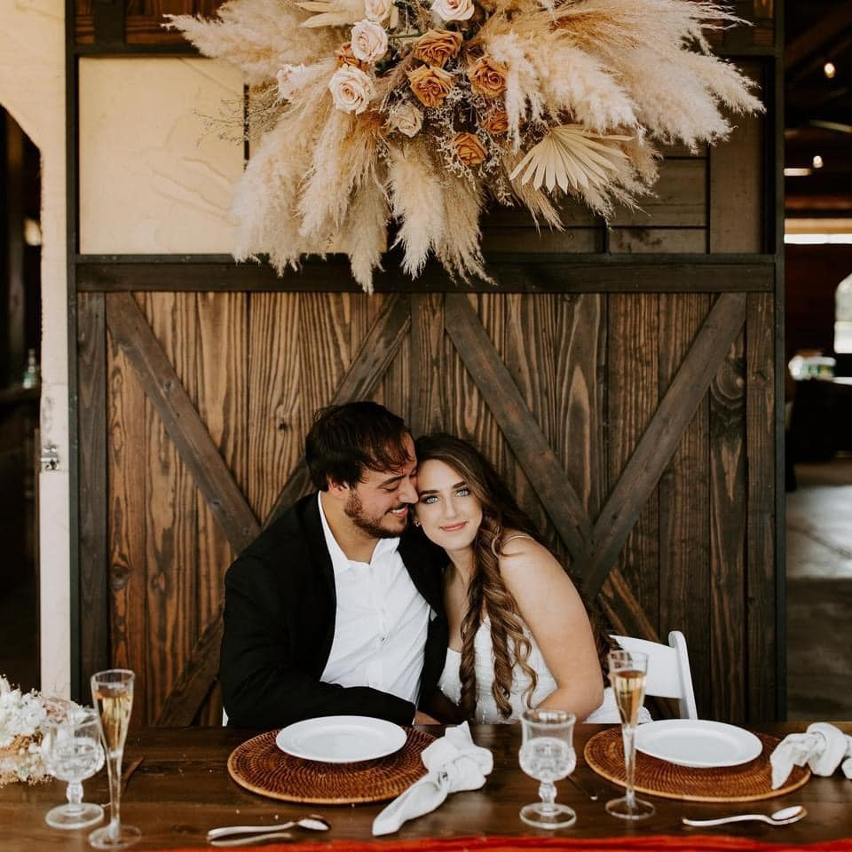 bride and groom sitting at a table during their wedding reception underneath a large flower arrangement on the wall