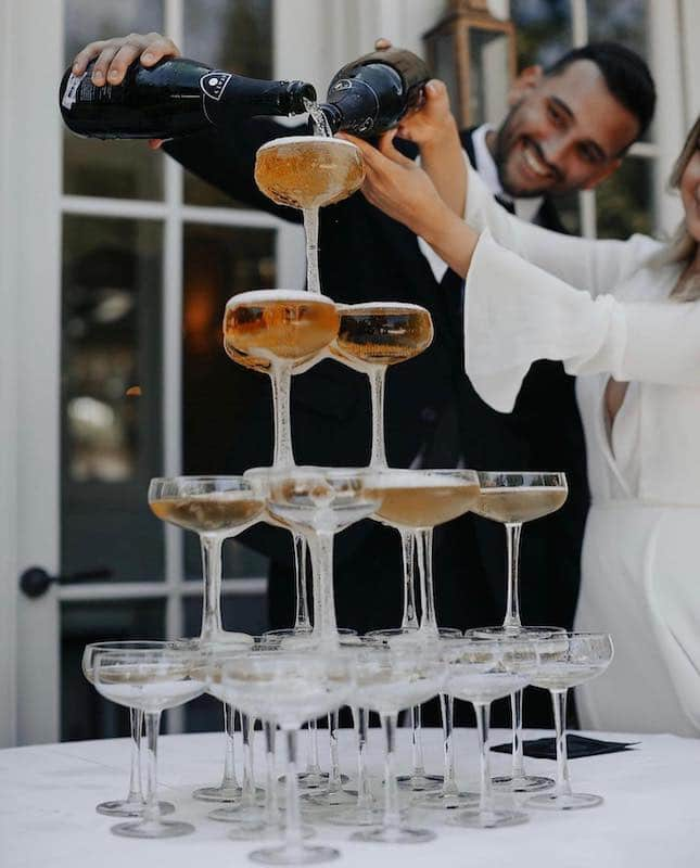 bride and groom pouring champagne into a tower of glasses