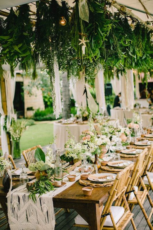 long table set up for wedding reception outside with green plants hanging from above