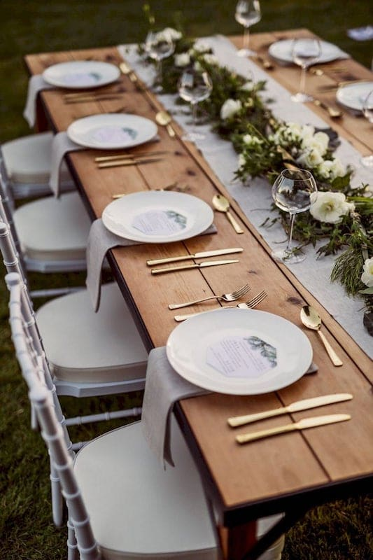 wooden table with white chairs set up for wedding reception