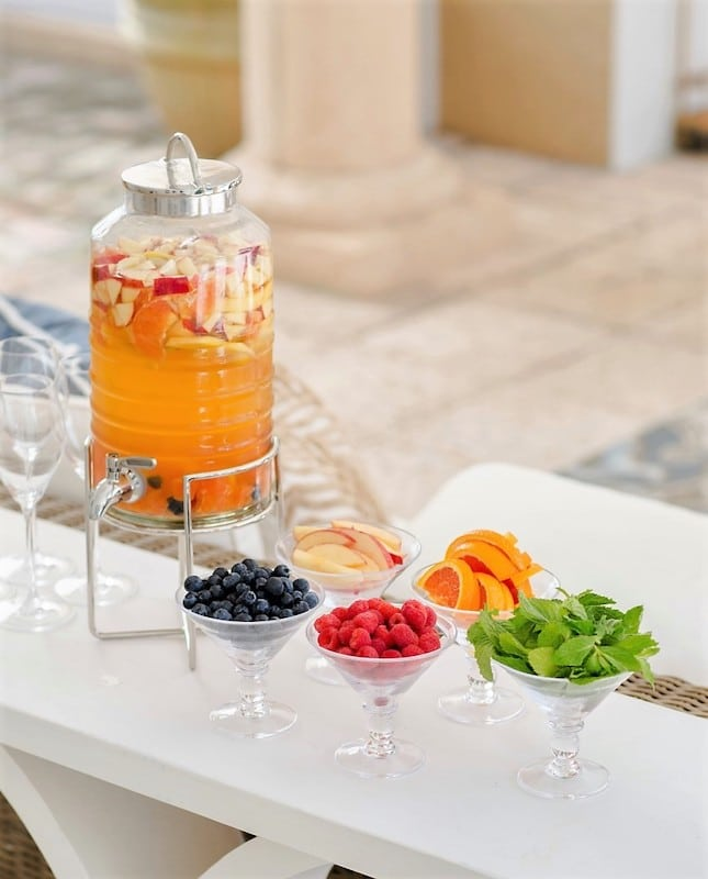 pitcher filled with sangria, with chopped fruit floating and more fruit available for garnish