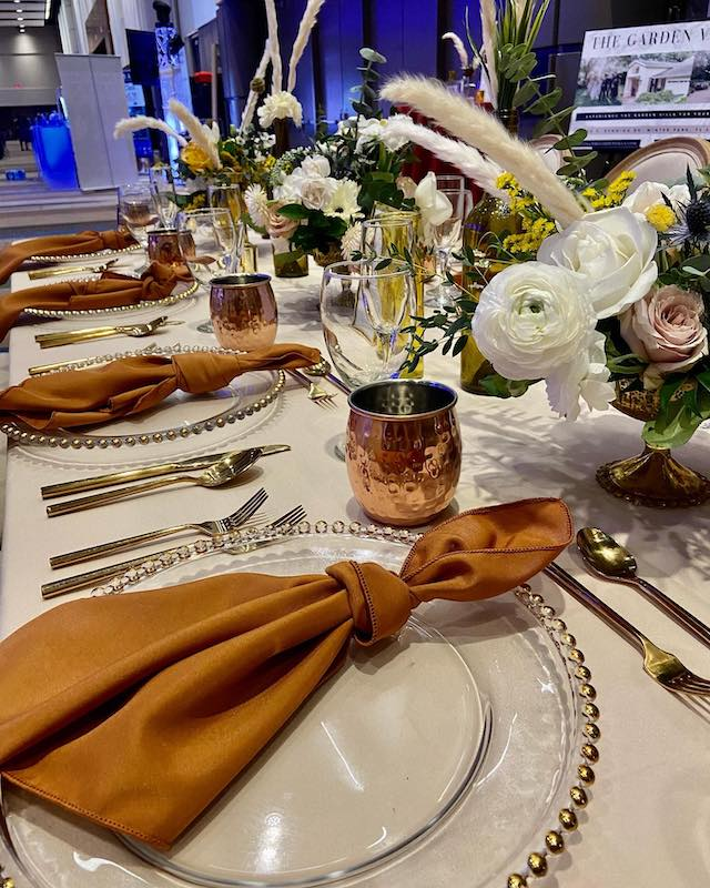 table decorated for wedding reception with copper mugs for moscow mules