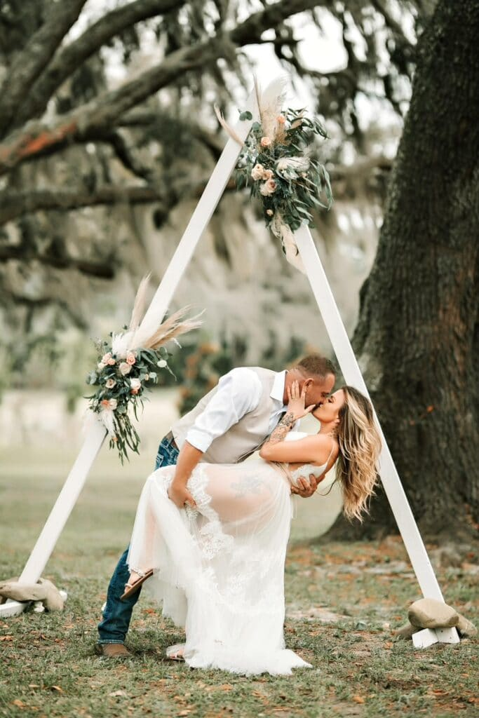 groom kissing his bride outside in front of white triangle arch decorated with flowers