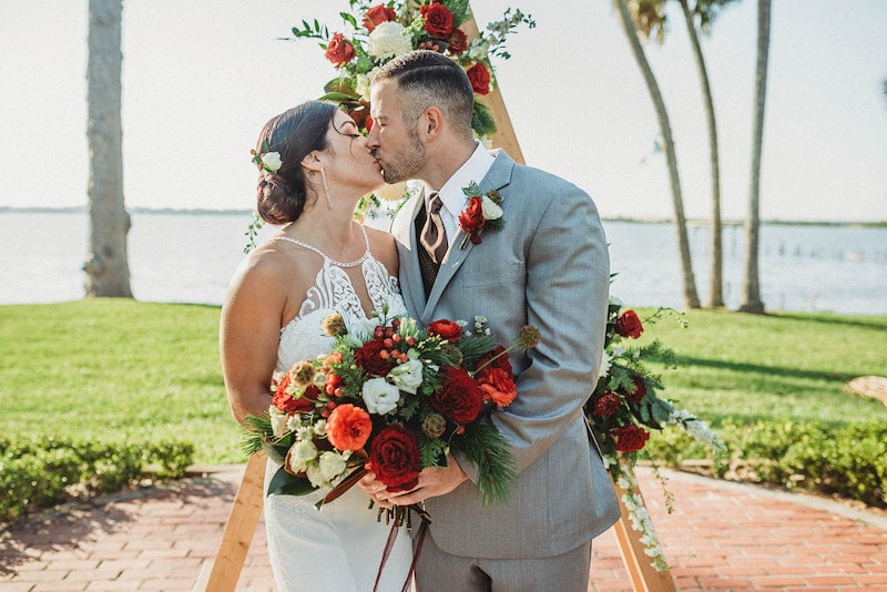 bride and groom kissing while holding flower bouquet from Fern and Curl Designs