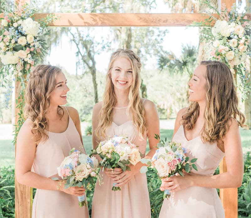 bride and her bridesmaids smiling while standing outside and holding their flower bouquets created by boutonniere