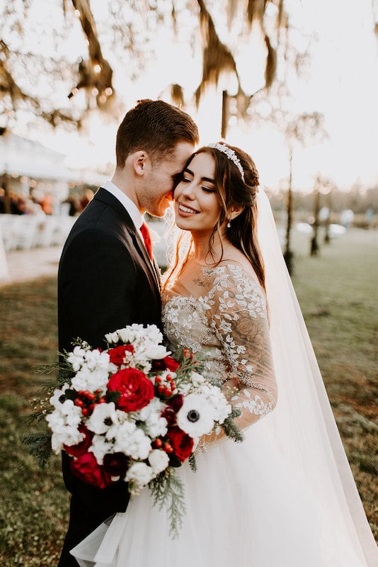 groom kissing his bride on the cheek while she holds her flower bouquet featuring white and red flowers