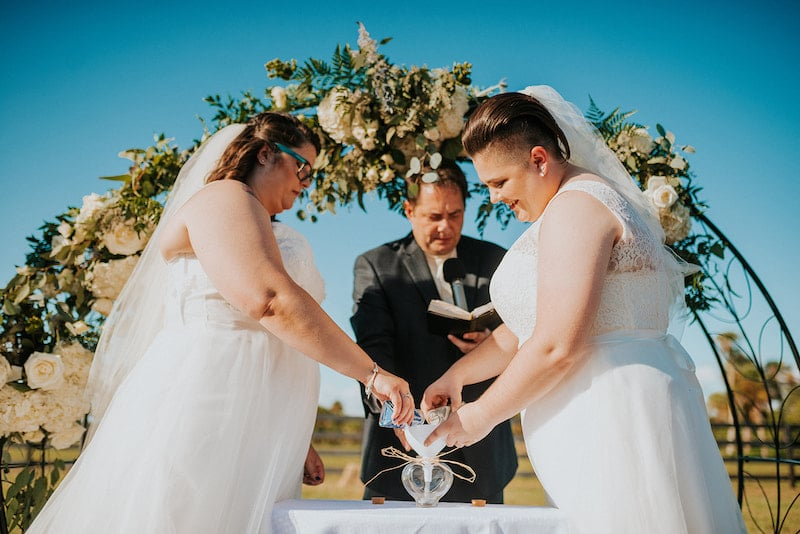 brides partaking in the sand ceremony during their wedding while standing in front of a flower covered arch