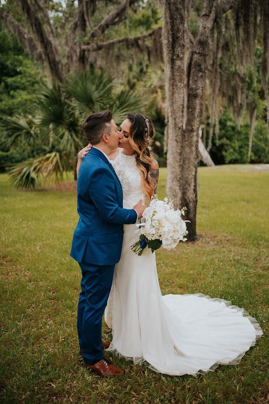 bride and groom kissing while standing in a field underneath large trees