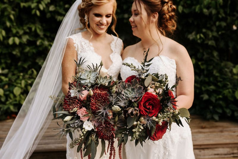 brides holding their matching flower bouquets created by Fern and Curl Designs