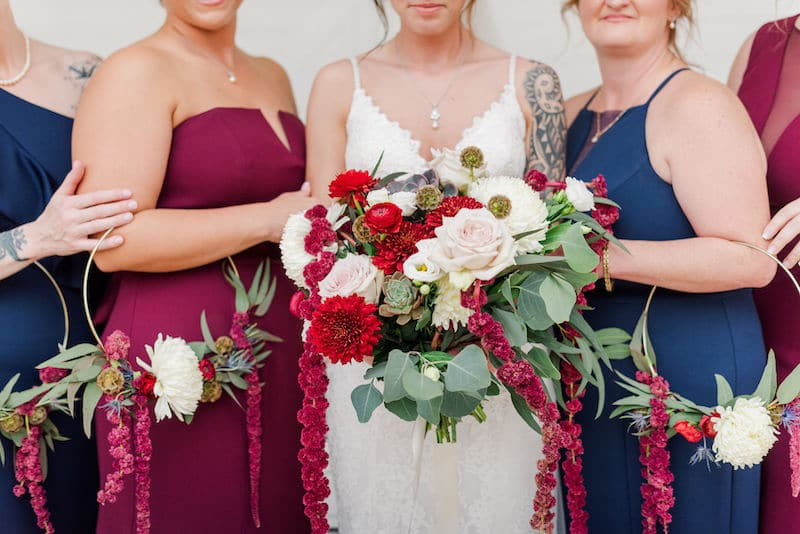 bride standing next to her bridesmaids while they each hold their matching bouquets created by Fern and Curl Designs