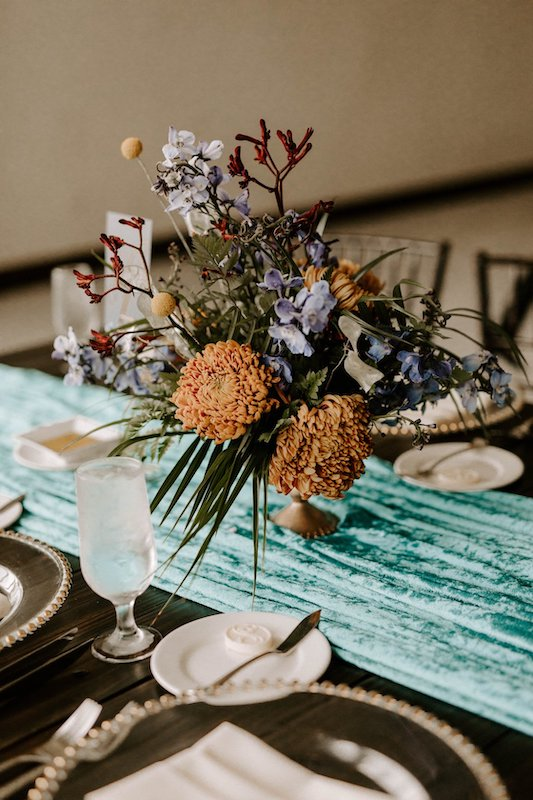 beautiful flower centerpieces placed on a teal runner for a wedding reception dinner table