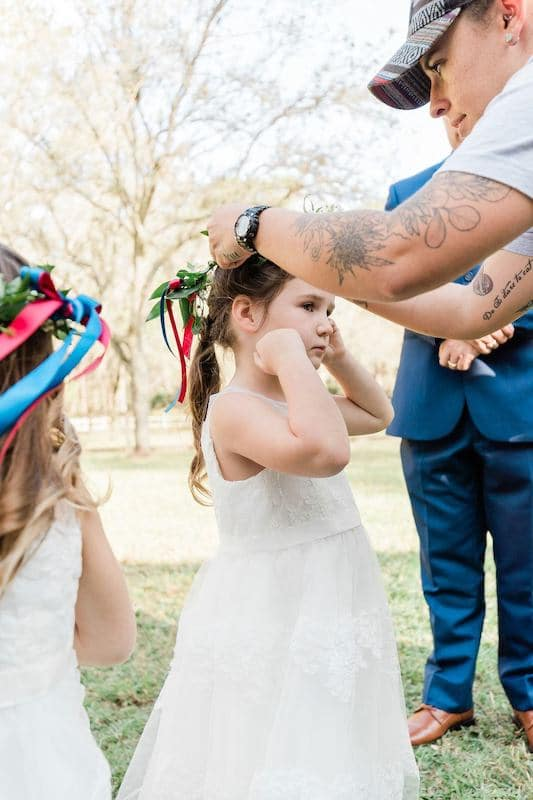 flower girls getting flowers and ribbons placed in their hair before the wedding ceremony