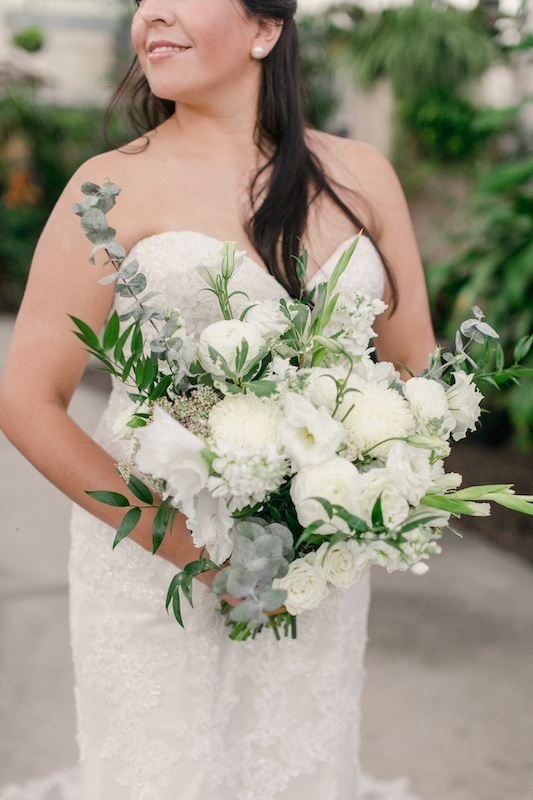 bride standing and holding her white flower bouquet created by Fern and Curl Designs