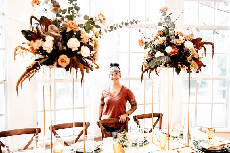 florist from Fern and Curl Designs standing between two tall flower centerpieces