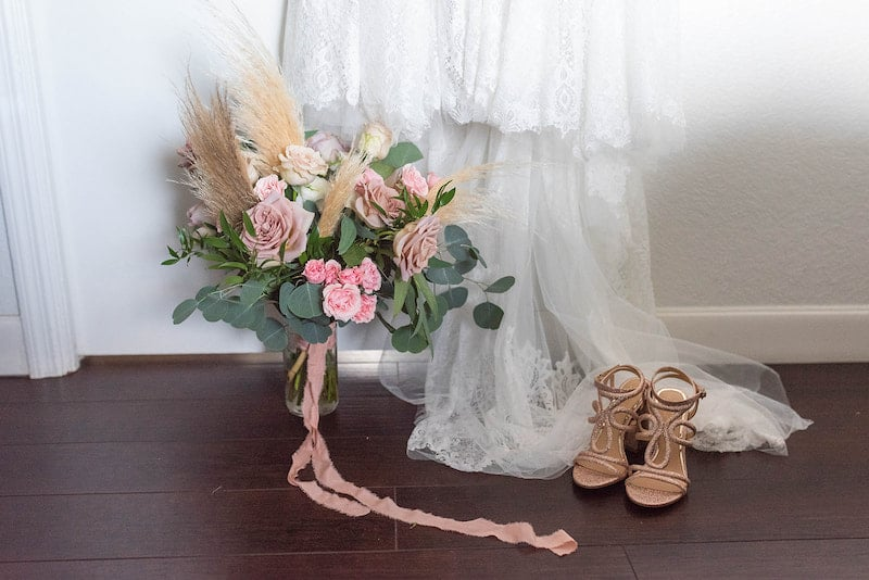 pink flowers in a vase sitting next to a wedding dress hung on the wall and the bride's shoes