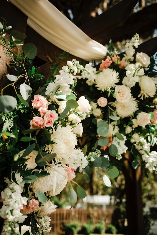 flower arrangement done by Fern and Curl Designs featuring white and pink flowers used as decorations during wedding ceremony