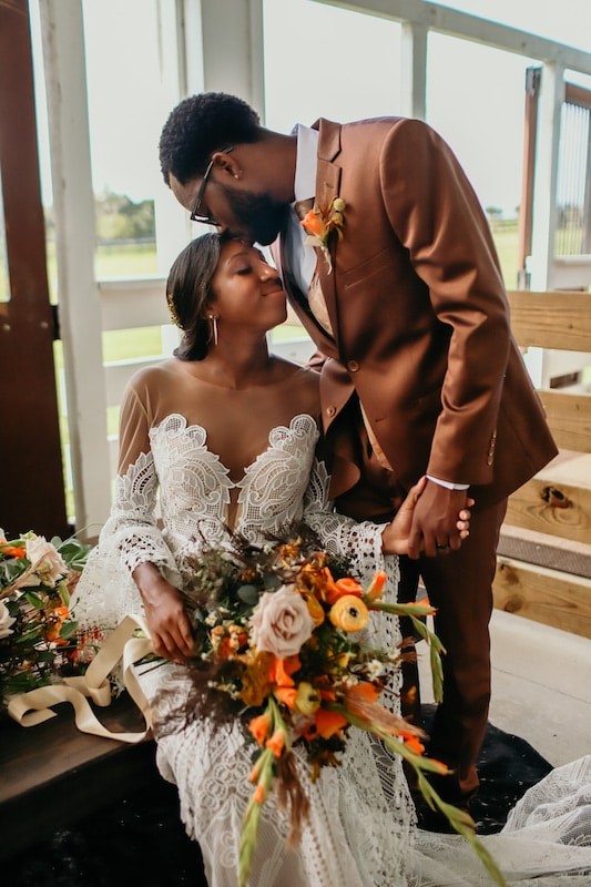 groom kissing his bride on her forehead while she sits holding her flower bouquet done by Fern and Curl Designs